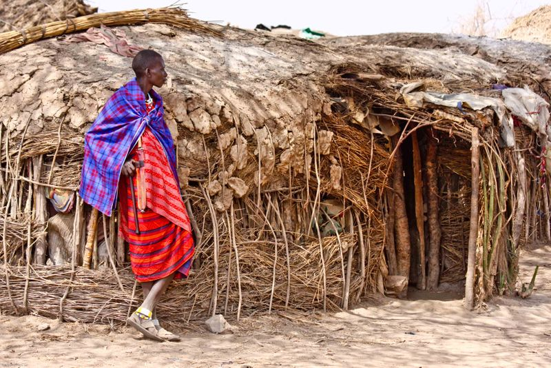 Masai man in front of the traditional nomadic hut