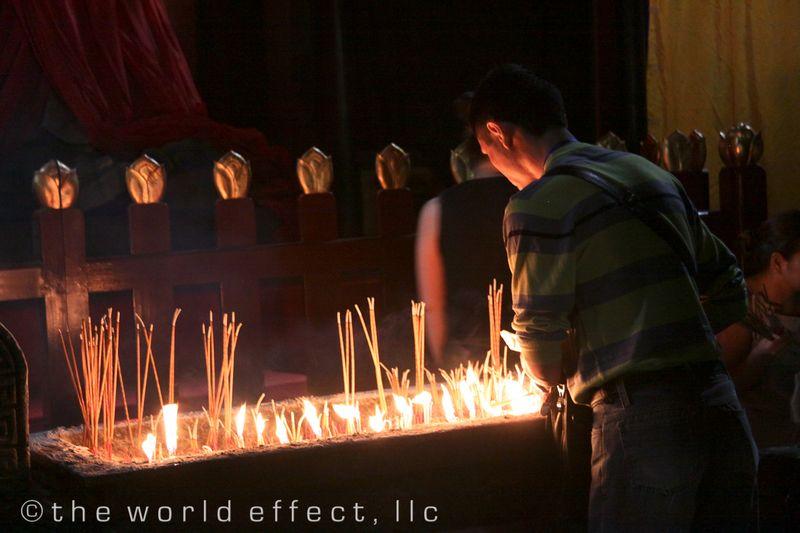 Chinese man lighting incense at Buddhist temple. Yangtzee RIver, China