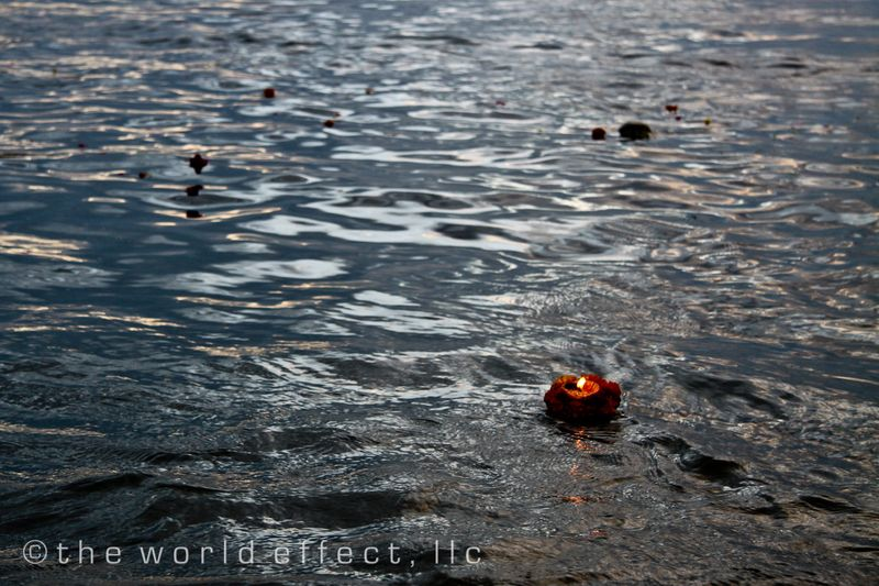 Candle floating on the Ganges at sunrise. Varanasi, India