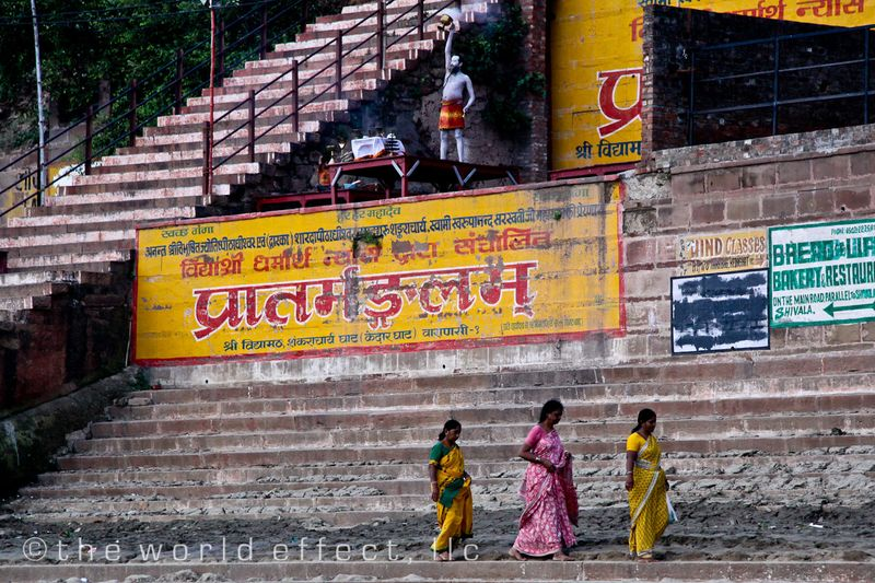 Woman walking along the Ganges below a holy man. Varanasi, India