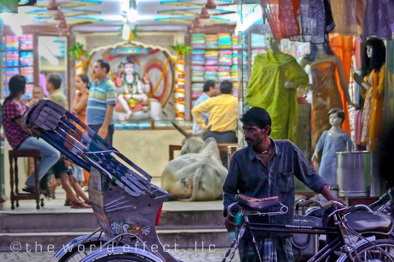 Richshaw Driver (Background: cow in clothing store) Evening in Varanasi, India